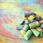 a collection of colorful sidewalk chalk is piled up on a rainbow drawing, outside on the pavement.