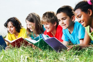 Group of kids reading books in the field.